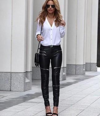 Comment porter: chemisier boutonné blanc, jean skinny en cuir noir, sandales à talons en cuir noires, sac bandoulière en cuir noir