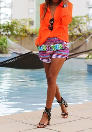 Comment porter: chemisier boutonné orange, short à fleurs multicolore, sandales à talons en cuir à clous noires, lunettes de soleil noires