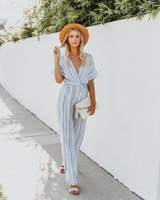 Comment porter: combinaison pantalon à rayures verticales bleu clair, sandales plates en cuir blanches, pochette en cuir blanche, chapeau de paille marron clair