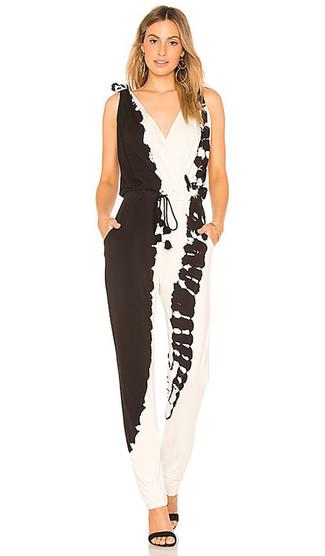 Comment porter: combinaison pantalon imprimé tie-dye noire et blanche, sandales à talons en daim noires, boucles d'oreilles dorées