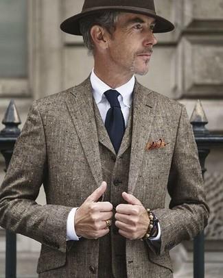 Comment porter: complet marron, chemise de ville blanche, chapeau en laine marron foncé, cravate en tricot bleu marine