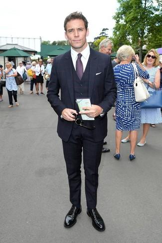 Comment porter: complet à carreaux bleu marine, chemise de ville blanche, chaussures derby en cuir noires, cravate imprimée pourpre foncé