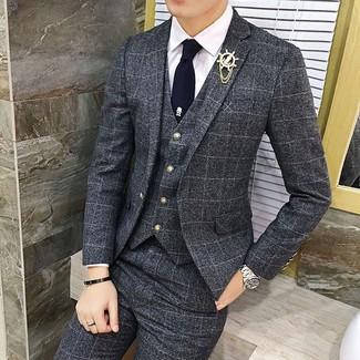 Comment porter: complet à carreaux gris foncé, chemise de ville blanche, cravate bleu marine, broche dorée