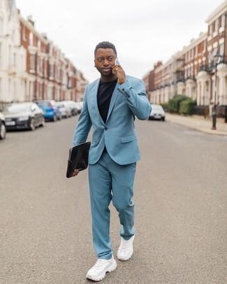 Tendances mode hommes: Marie un costume bleu clair avec un t-shirt à col rond noir si tu recherches un look stylé et soigné. Une paire de chaussures de sport blanches apporte une touche de décontraction à l'ensemble.