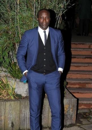 Tenue de Dermot O'Leary: Costume bleu marine, Cardigan noir, Chemise de ville blanche, Cravate bleu marine