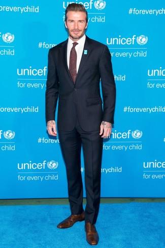 Tenue de David Beckham: Costume à rayures verticales bleu marine, Chemise de ville blanche, Chaussures richelieu en cuir marron, Cravate imprimée cachemire bordeaux