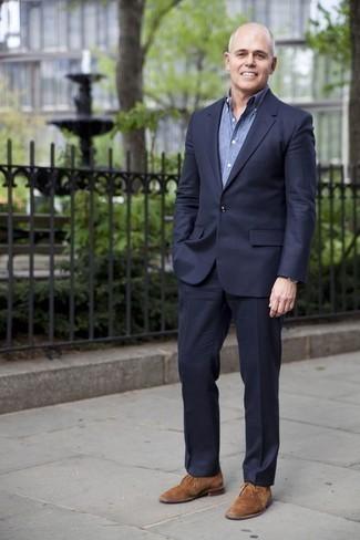 Comment porter une chemise de ville en chambray bleue: Pense à porter une chemise de ville en chambray bleue et un costume bleu marine pour un look classique et élégant. Tu veux y aller doucement avec les chaussures? Complète cet ensemble avec une paire de des bottines chukka en daim marron clair pour la journée.