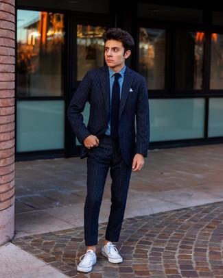 Comment porter: costume en laine à rayures verticales bleu marine, chemise en jean bleue, baskets basses en toile blanches, cravate noire