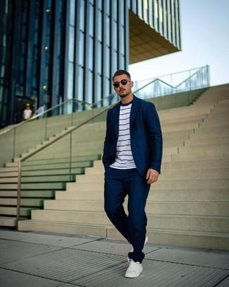 Comment porter: costume bleu marine, t-shirt à col rond à rayures horizontales blanc et bleu marine, baskets basses en cuir blanches, lunettes de soleil noires