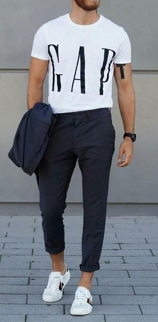 Comment porter: costume bleu marine, t-shirt à col rond imprimé blanc et noir, baskets basses en cuir blanches, montre noire