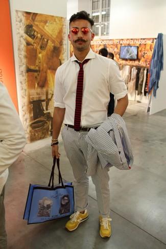 Comment porter: costume en seersucker à rayures verticales bleu marine et blanc, chemise à manches longues blanche, baskets basses en daim jaunes, sac fourre-tout en toile imprimé bleu