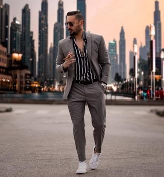Comment porter un costume gris: Harmonise un costume gris avec une chemise à manches longues à rayures verticales noire et blanche pour une silhouette classique et raffinée. Si tu veux éviter un look trop formel, fais d'une paire de des baskets basses blanches ton choix de souliers.