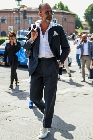 Comment porter des baskets basses en toile blanches: Marie un costume bleu marine avec une chemise à manches longues blanche pour dégager classe et sophistication. Une paire de des baskets basses en toile blanches apportera un joli contraste avec le reste du look.