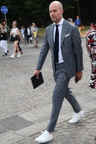 Comment porter une cravate en tricot bleu marine: Pense à porter un costume à rayures verticales gris et une cravate en tricot bleu marine pour une silhouette classique et raffinée. D'une humeur créatrice? Assortis ta tenue avec une paire de des baskets basses blanches.