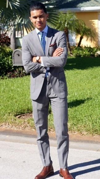 Comment porter une pochette de costume á pois bordeaux: Opte pour un costume gris avec une pochette de costume á pois bordeaux pour affronter sans effort les défis que la journée te réserve. Fais d'une paire de des bottes habillées en cuir tabac ton choix de souliers pour afficher ton expertise vestimentaire.