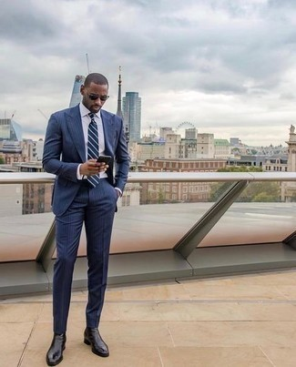 Comment s'habiller à 30 ans: Harmonise un costume à rayures verticales bleu marine avec une chemise de ville blanche pour une silhouette classique et raffinée. Si tu veux éviter un look trop formel, fais d'une paire de bottines chelsea en cuir noires ton choix de souliers.