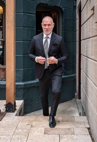 Comment porter un costume gris foncé: Harmonise un costume gris foncé avec une chemise de ville blanche pour dégager classe et sophistication. Mélange les styles en portant une paire de des chaussures derby en cuir noires.