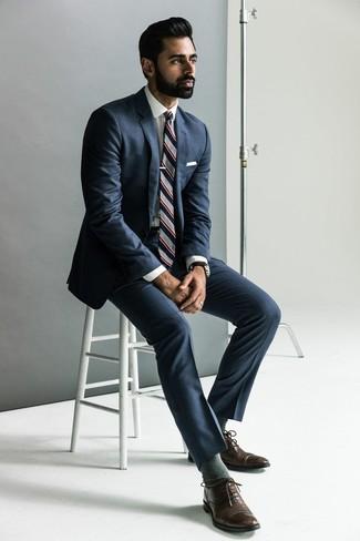 Comment porter: costume bleu marine, chemise de ville blanche, chaussures richelieu en cuir marron foncé, cravate à rayures verticales grise