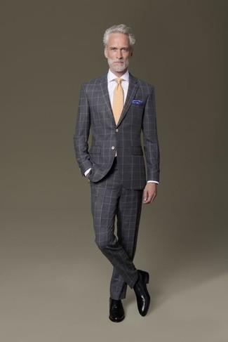 Comment s'habiller après 50 ans: Sois au sommet de ta classe en portant un costume à carreaux gris foncé et une chemise de ville blanche. Une paire de des chaussures richelieu en cuir noires est une option parfait pour complèter cette tenue.