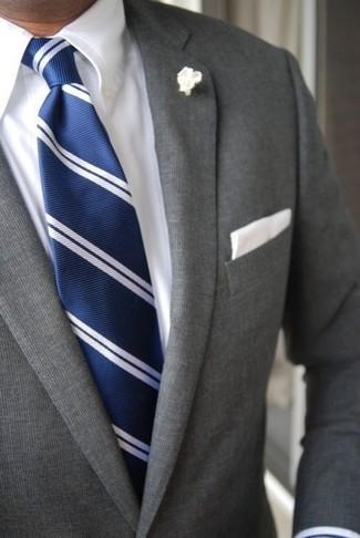 Comment porter: costume gris, chemise de ville blanche, cravate à rayures verticales bleu marine et blanc, pochette de costume blanche