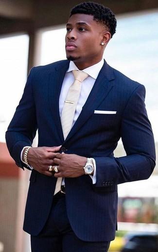 Comment porter: costume à rayures verticales bleu marine, chemise de ville blanche, cravate beige, pochette de costume blanche