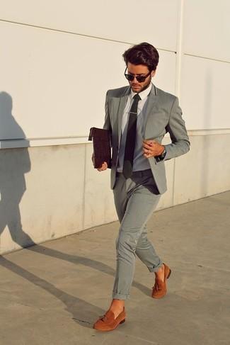 Comment porter une pochette en cuir marron foncé: Porte un costume gris et une pochette en cuir marron foncé pour une tenue confortable aussi composée avec goût. Jouez la carte classique pour les chaussures et complète cet ensemble avec une paire de des mocassins à pampilles en daim tabac.