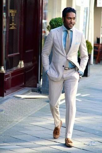 Comment s'habiller à 30 ans: Choisis un costume en lin beige et une chemise de ville en chambray bleu clair pour un look classique et élégant. Jouez la carte décontractée pour les chaussures et choisis une paire de des mocassins à pampilles en daim marron clair.