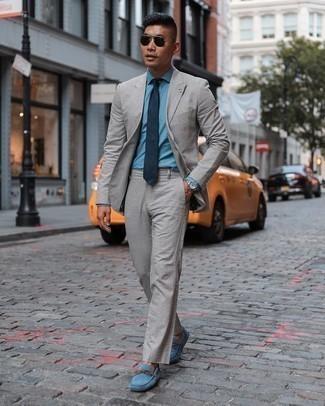 Comment s'habiller pour un style elégantes: Essaie d'harmoniser un costume gris avec une chemise de ville en chambray bleu clair pour un look pointu et élégant. Pourquoi ne pas ajouter une paire de mocassins en daim bleus à l'ensemble pour une allure plus décontractée?