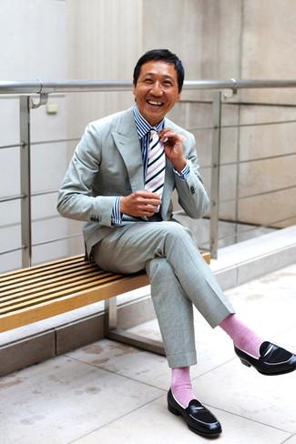 Comment porter: costume gris, chemise de ville à rayures verticales blanc et bleu marine, slippers en cuir noirs, cravate à rayures verticales blanche et noire