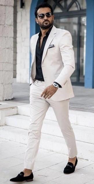 Comment porter un costume blanc: Marie un costume blanc avec une chemise de ville noire pour dégager classe et sophistication. Si tu veux éviter un look trop formel, choisis une paire de des slippers en velours noirs.