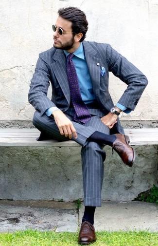 Comment porter: costume à rayures verticales gris, chemise en jean bleue, chaussures richelieu en cuir marron, cravate imprimée pourpre