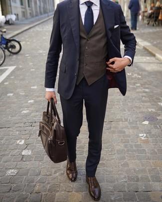 Comment porter une serviette en cuir marron foncé: Essaie d'associer un costume bleu marine avec une serviette en cuir marron foncé pour obtenir un look relax mais stylé. Habille ta tenue avec une paire de des chaussures brogues en cuir marron foncé.