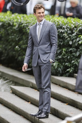 Tenue de Jamie Dornan: Costume gris, Chemise de ville blanche, Chaussures derby en cuir noires, Cravate grise