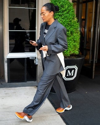 Comment porter: costume gris foncé, t-shirt à col rond imprimé noir et blanc, chaussures de sport tabac