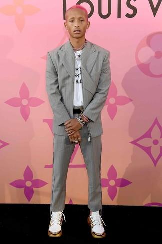 Comment porter: costume à rayures verticales gris, t-shirt à col rond imprimé blanc et noir, chaussures de sport blanches, ceinture en cuir noire