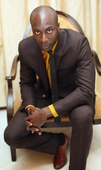 Tenue de Dermot O'Leary: Costume marron foncé, Chemise de ville orange, Chaussures richelieu en cuir tabac, Cravate à rayures verticales marron foncé