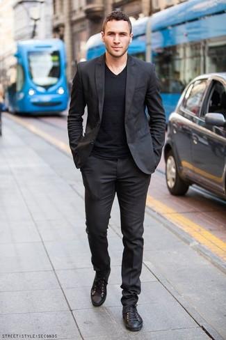 Comment porter un costume noir: Pense à opter pour un costume noir et un t-shirt à col en v noir pour achever un look habillé mais pas trop. Jouez la carte décontractée pour les chaussures et complète cet ensemble avec une paire de des baskets basses en cuir noires.