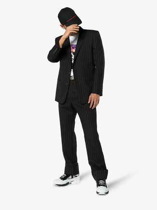 Comment porter: costume à rayures verticales noir, t-shirt à col rond imprimé blanc, chaussures de sport blanches, casquette de base-ball noire