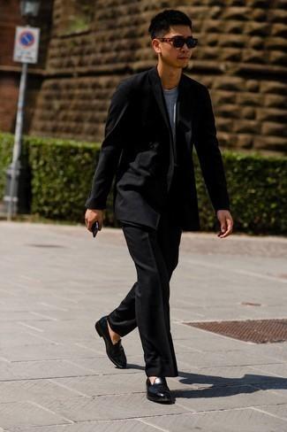 Tendances mode hommes: Associer un costume noir avec un t-shirt à col rond gris est une option avisé pour une journée au bureau. Complète cet ensemble avec une paire de slippers en cuir noirs pour afficher ton expertise vestimentaire.