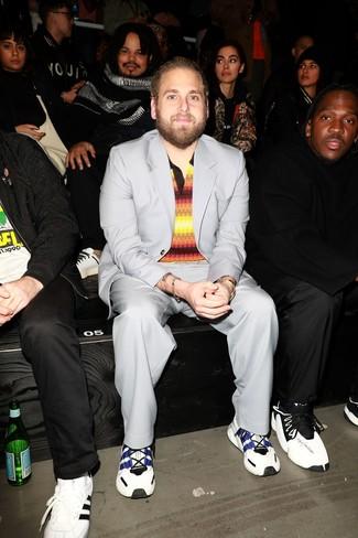 Comment porter: costume gris, polo à rayures horizontales multicolore, chaussures de sport blanc et bleu marine, montre dorée