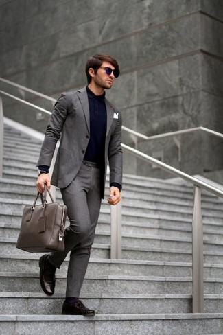 Comment porter une serviette en cuir grise: Pense à marier un costume gris foncé avec une serviette en cuir grise pour une tenue confortable aussi composée avec goût. Complète cet ensemble avec une paire de des mocassins à pampilles en cuir marron foncé pour afficher ton expertise vestimentaire.