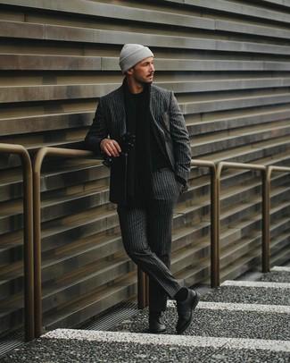Comment porter: costume à rayures verticales gris foncé, pull à col rond noir, chaussures derby en cuir noires, bonnet gris