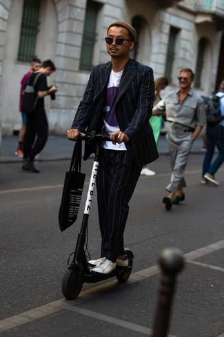 Comment porter: costume à rayures verticales noir, t-shirt à col rond imprimé blanc, baskets basses en cuir blanches, sac fourre-tout en toile imprimé noir