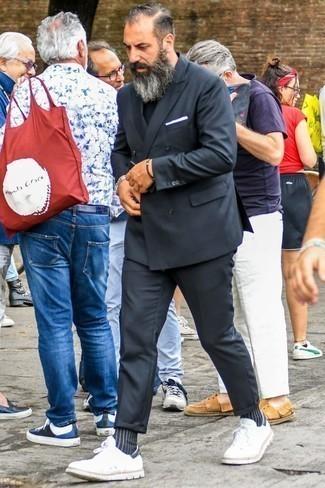 Tendances mode hommes: Marie un costume gris foncé avec un t-shirt à col rond noir si tu recherches un look stylé et soigné. Si tu veux éviter un look trop formel, choisis une paire de des baskets basses blanches.