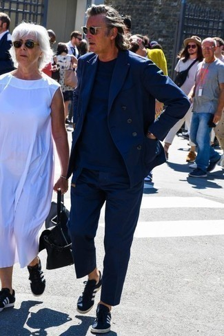 Comment porter un t-shirt à col rond bleu marine: Pense à associer un t-shirt à col rond bleu marine avec un costume bleu marine pour un look idéal au travail. Jouez la carte décontractée pour les chaussures et assortis cette tenue avec une paire de des baskets basses en toile bleu marine et blanc.