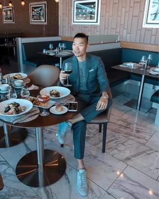 Tendances mode hommes: Essaie d'associer un costume à rayures verticales bleu canard avec un t-shirt à col rond gris pour créer un look chic et décontracté. Jouez la carte décontractée pour les chaussures et choisis une paire de baskets basses en cuir blanches.