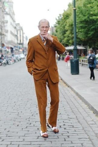 Comment s'habiller après 60 ans: Harmonise un costume tabac avec une chemise de ville grise pour une silhouette classique et raffinée. Jouez la carte décontractée pour les chaussures et assortis cette tenue avec une paire de chaussures derby en cuir blanches.