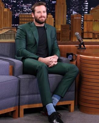 Comment porter: costume vert foncé, pull à col rond noir, chaussures richelieu en cuir noires, chaussettes bleues