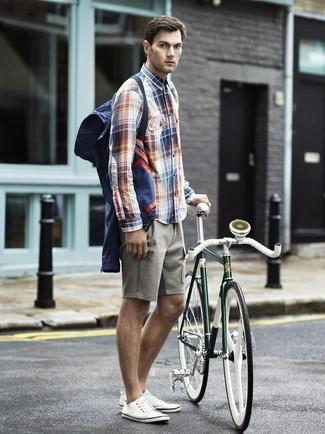 Les journées chargées nécessitent une tenue simple mais stylée, comme un coupe-vent bleu marine Napapijri et un short gris. Cette tenue se complète parfaitement avec une paire de des baskets basses en toile blanches.