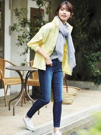 Comment porter: coupe-vent jaune, jean skinny bleu marine, baskets basses en toile blanches, sac fourre-tout de paille marron clair